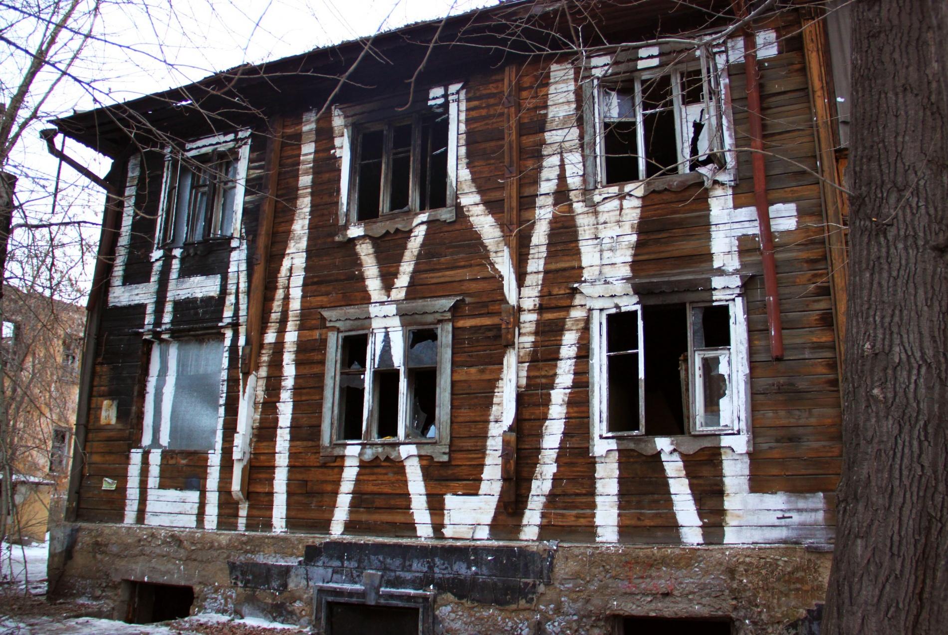 Заброшенный дом, на стену которого нанесена надпись, выглядит так, будто жильцы покинули его не так давно.